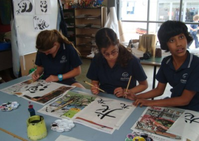 Year Six students trying their hand at Chinese calligraphy.